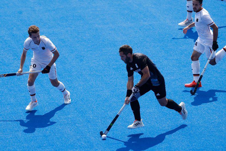 Agustín Mazzilli maniobra con la bocha ante la marca de los defensores alemanes durante el partido entre los Leones y los teutones, por cuartos de final del hockey sobre césped de Tokio 2020.