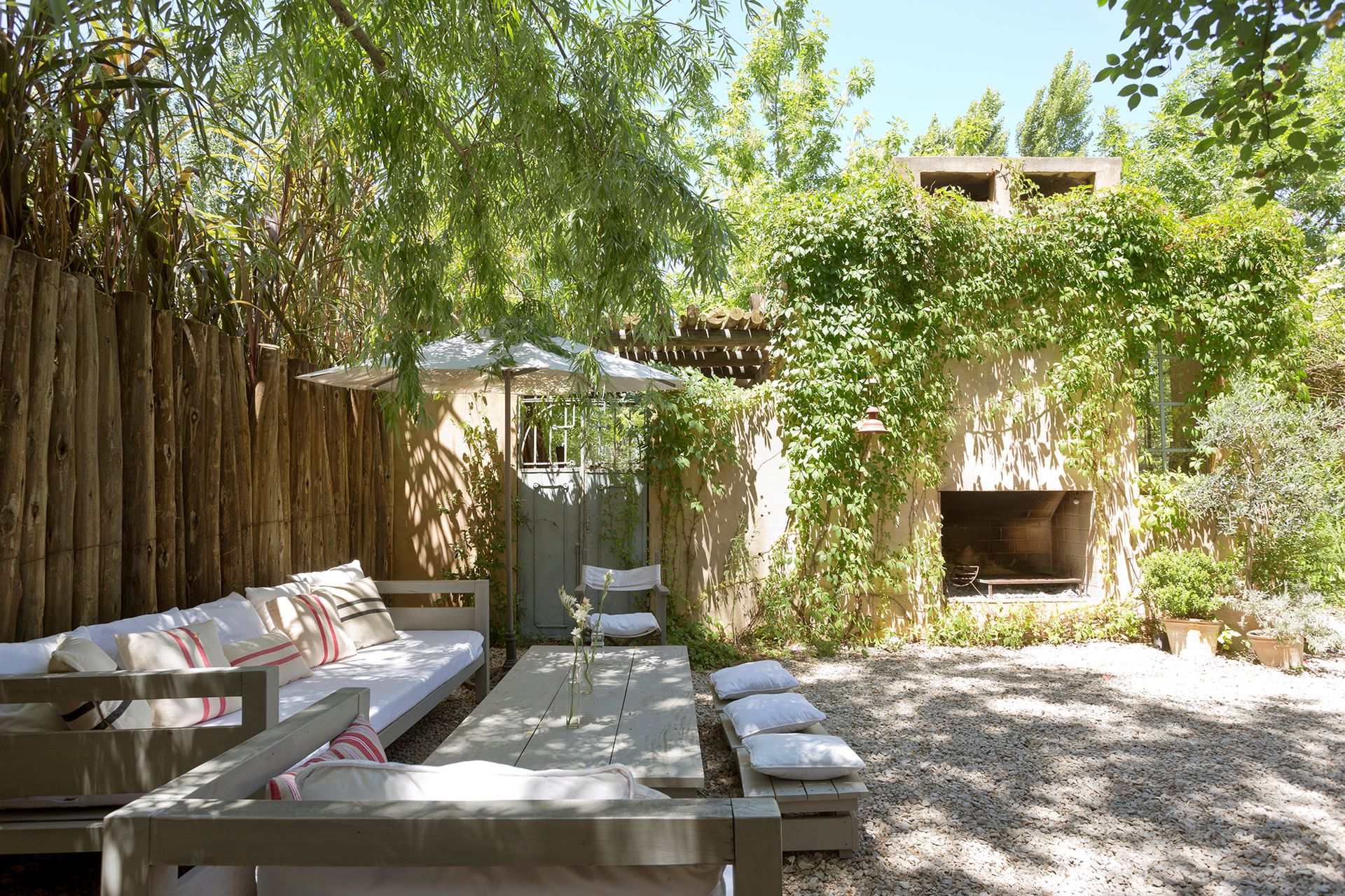 La mesa de este patio la hizo Luciano, el marido de Consuelo, con unos tablones de madera de anchico patinados luego en un tono gris pastel.
