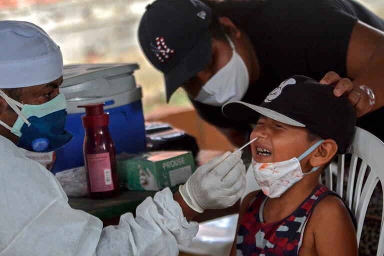 Un trabajador de salud toma una muestra de hisopado de un niño para realizar una prueba de coronavirus en la comunidad ribereña de Bela Vista do Jaraqui, Manaos, estado de Amazonas, Brasil, el 18 de enero de 2021