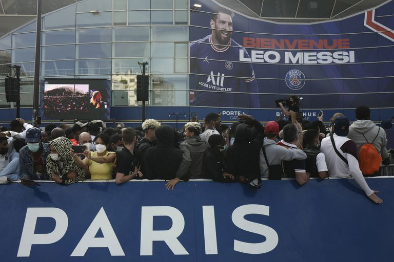 Paris Saint-Germain supporters gather outside the Parc des Princes stadium before Lionel Messi's press conference Wednesday, Aug. 11, 2021 in Paris. Lionel Messi finally signed his eagerly anticipated Paris Saint-Germain contract on Tuesday night to complete the move that confirms the end of a career-long association with Barcelona and sends PSG into a new era. (AP Photo/Rafael Yaghobzadeh)