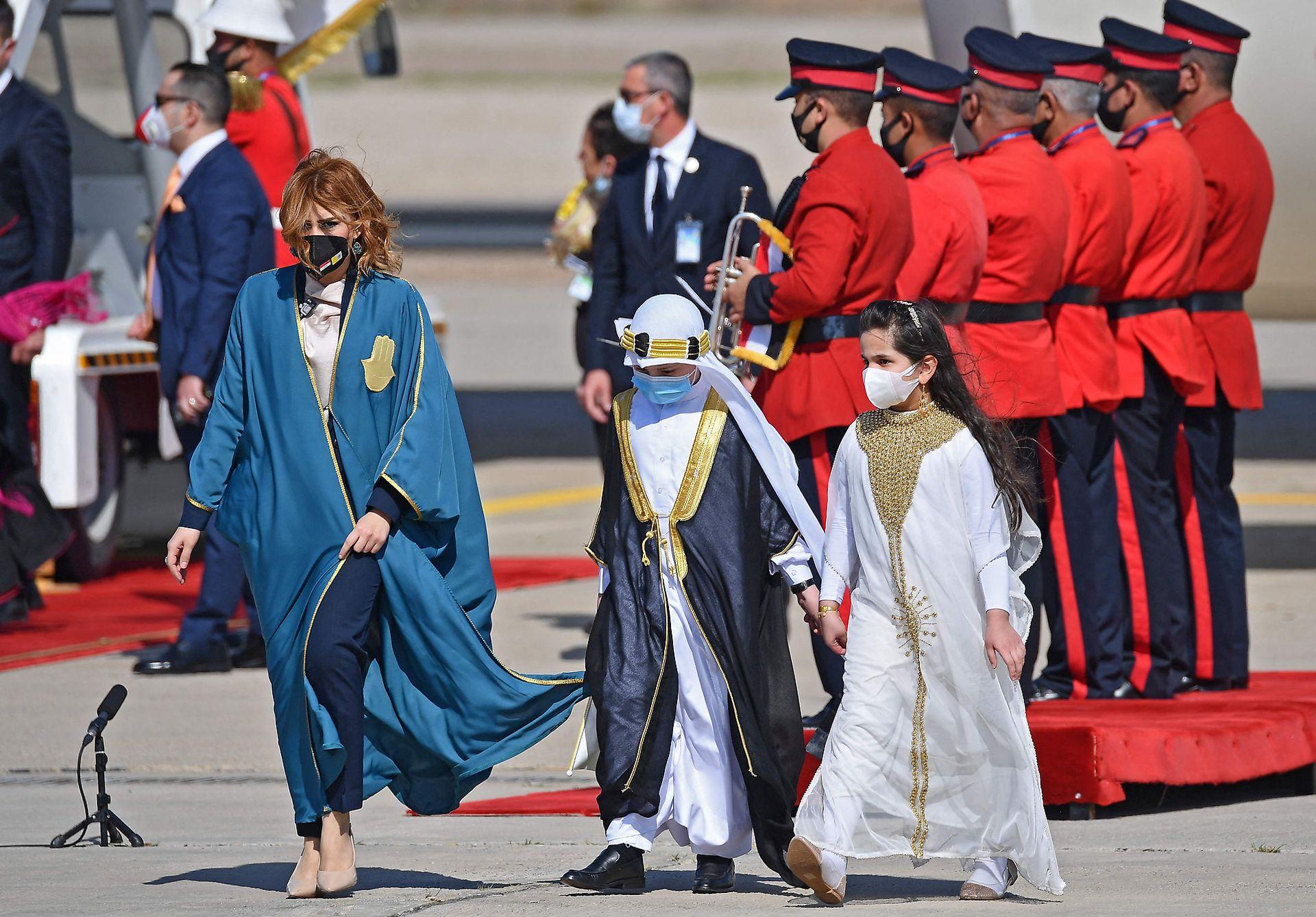 Una niña y un niño participan de la ceremonia del bienvenida al Papa en el aeropuerto de Bagdad