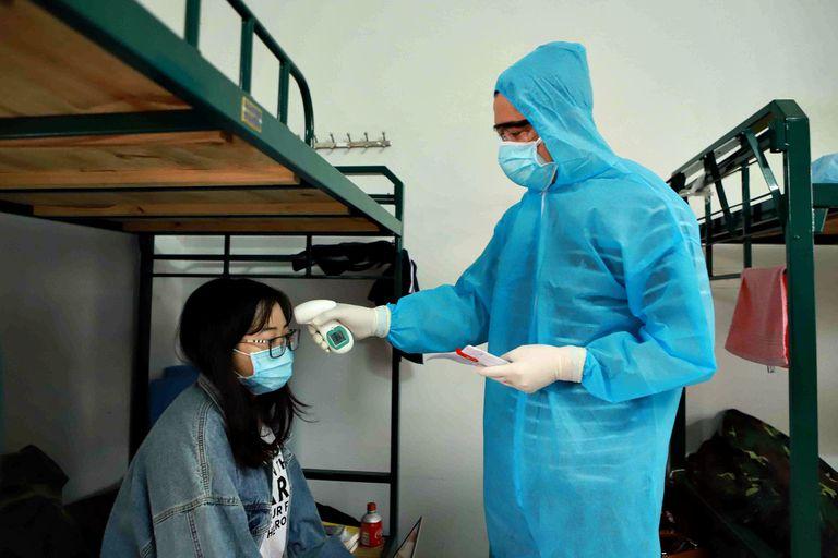 (200317) -- HANOI, 17 marzo, 2020 (Xinhua) -- Imagen del 16 de marzo de 2020 de un doctor verificando la temperatura de una mujer en una instalación de cuarentena, en la provincia de Vinh Phuc, en el norte de Vietnam. El Ministerio de Salud de Vietnam dijo el martes por la tarde que cinco personas locales más dieron positivo para el nuevo coronavirus, trayendo el total de casos confirmados de COVID-19 en el país a 66. (Xinhua/VNA) (eb) (rtg)