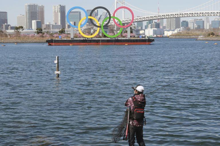 Un pescador disfruta de la pesca con los anillos olímpicos flotando en el agua en Tokio, martes 23 de febrero de 2021