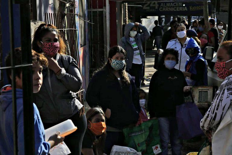 Una fila de personas espera frente a uno de los comedores a que se inicie el reparto de alimentos