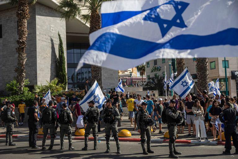 Agentes de la policía fronteriza paramilitar israelí montan guardia mientras manifestantes judíos de derecha exigen la liberación de tres judíos arrestados por asesinato frente al Tribunal de Distrito en Lod