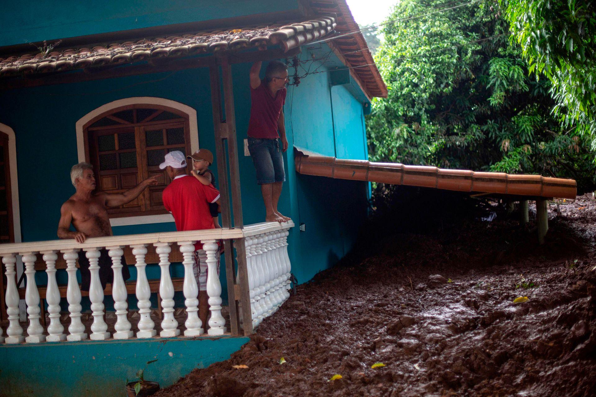 Una familia del pueblo Parque da Cachoeira observa los daños que produjo el barro en su vivienda