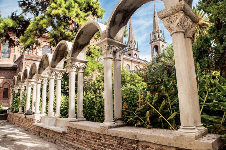 Claustro de la abadía de San Benito Abad y detrás, las agudas torres de la iglesia homónima