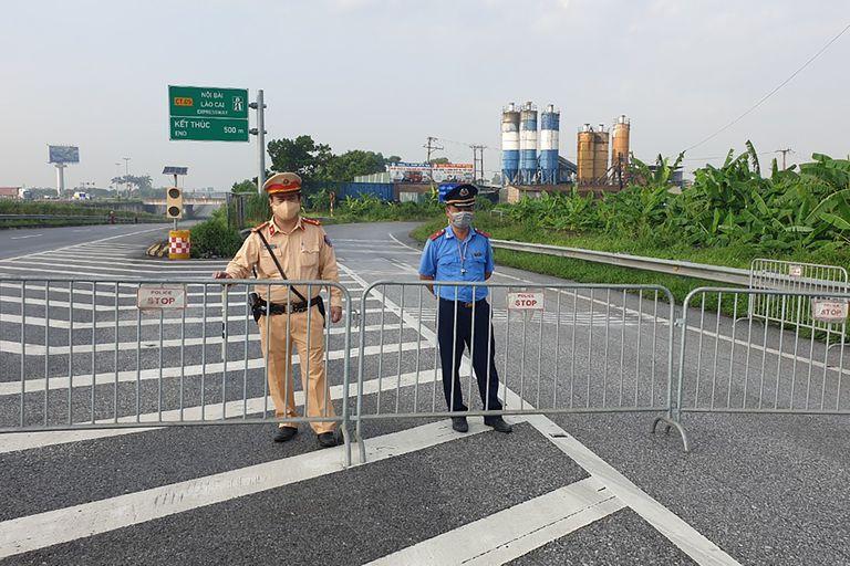 Policías montan guardia detrás de barricadas para controlar el tráfico en Hanoi, Vietnam, el sábado, 24 de julio del 2021. Vietnam anunció un encierro de 15 días en la capital  en medio de un aumento de los casos de coronavirus. (AP Foto/Hieu Dinh)