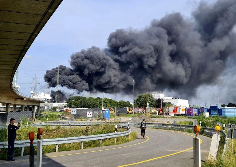 Vehículos de emergencias de bomberos, rescatistas y policías estacionados cerca del acceso al recinto industrial Chempark, sobre el que se alza una negra humareda, en Leverkusen, Alemania, el martes 27 de julio de 2021. (Oliver Berg/dpa via AP)
