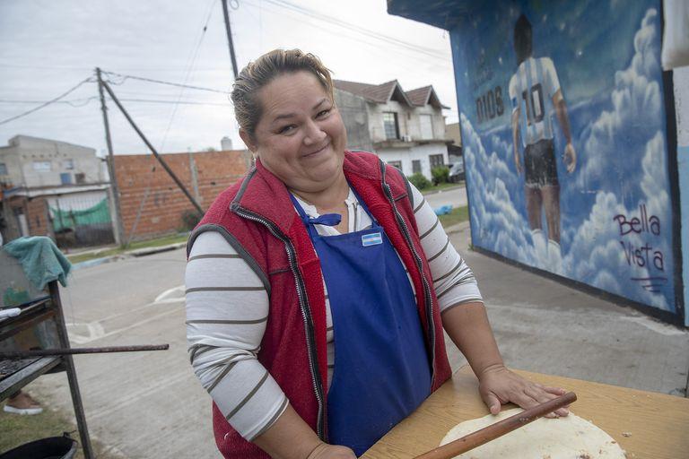 """Carmen Segovia prepara tortillas justo frente al cementerio Jardín Bella Vista. Detrás suyo hay un mural en el que se lee: """"Aquí descansa Dios"""", hecho por el artista Damián Ferro"""