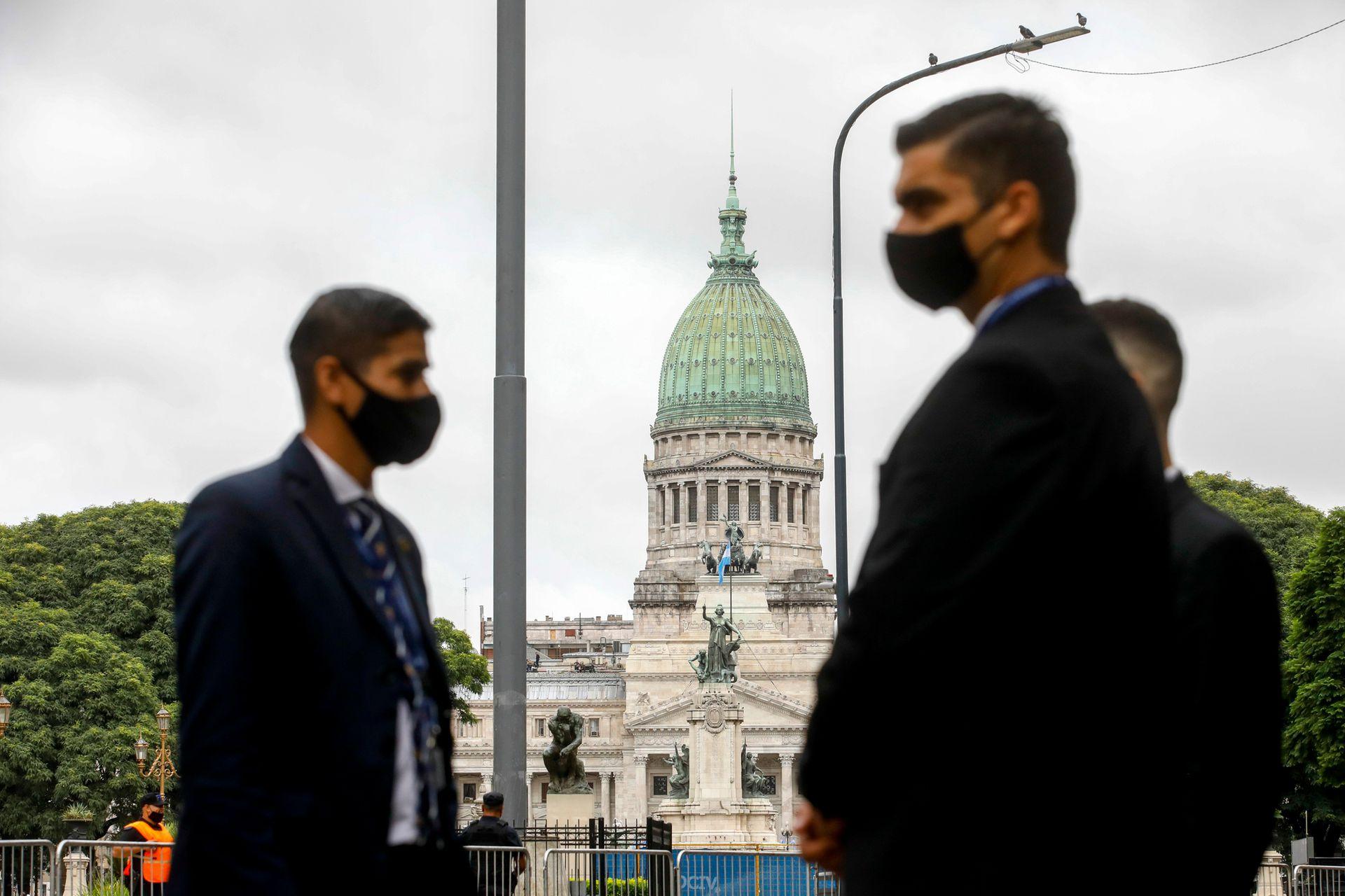 Gente con barbijos, de fondo el Congreso de La Nación, poco antes del inicio de la Apertura de las Sesiones Legislativas
