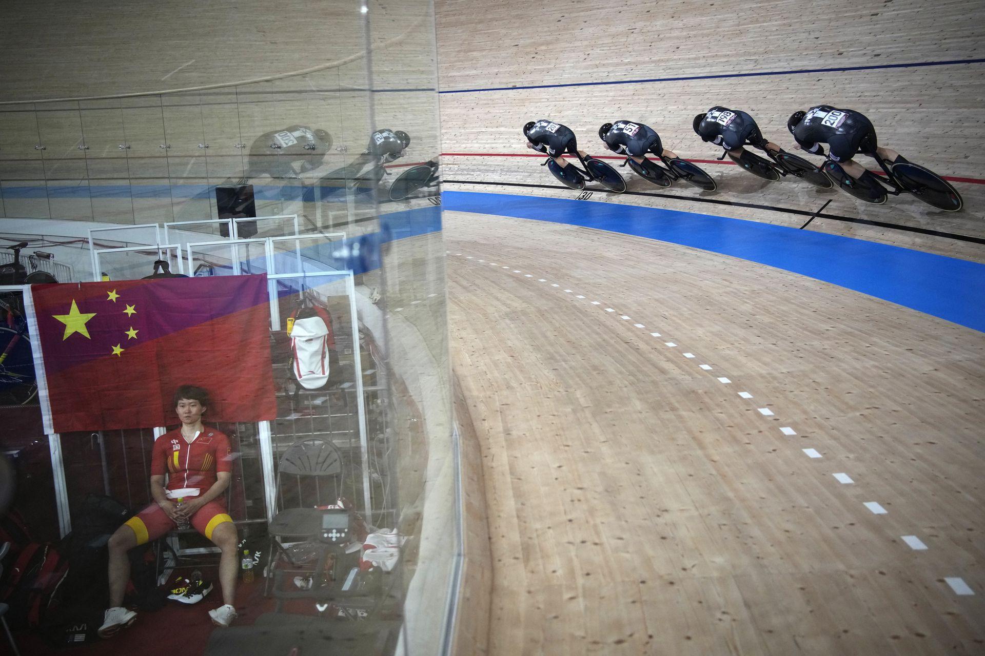 El equipo de Nueva Zelanda compite mientras Tianshi Zhong del equipo de China, a la izquierda, se toma un descanso durante una eliminatoria de clasificación para la persecución por equipos femeninos de ciclismo en pista