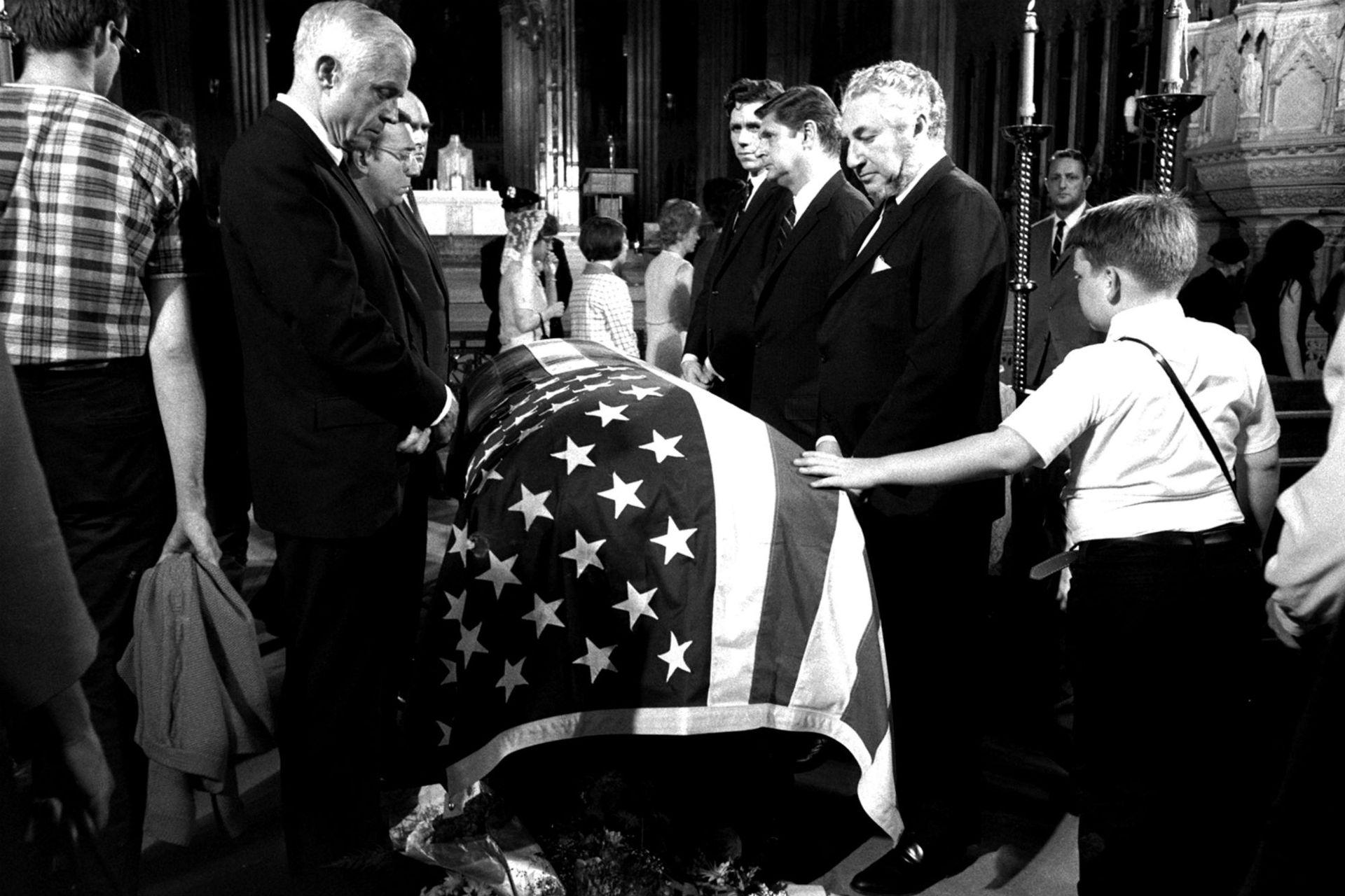 Un chico toca el féretro de Kennedy durante su funeral en la catedral de San Patricio en Nueva York
