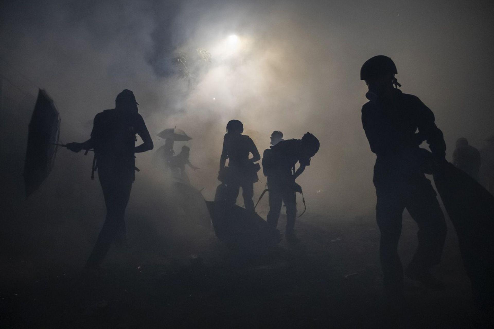 Los manifestantes son alcanzado por los gases intentan protegerse en la universidad de Hong Kong