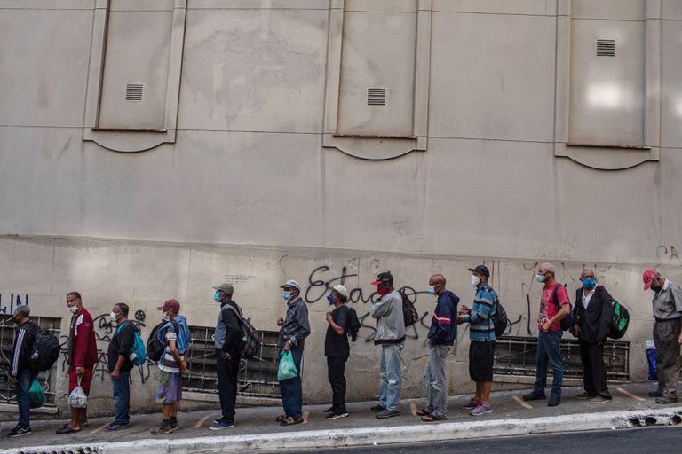 Una larga fila de indigentes a la espera de recibir alimentos de una organización humanitaria