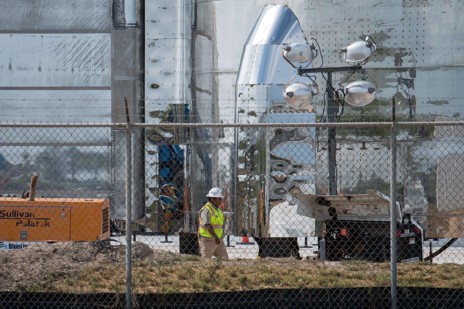Un trabajador camina por la base de un prototipo de nave espacial Starship de SpaceX en las instalaciones de lanzamiento de la compañía en Texas