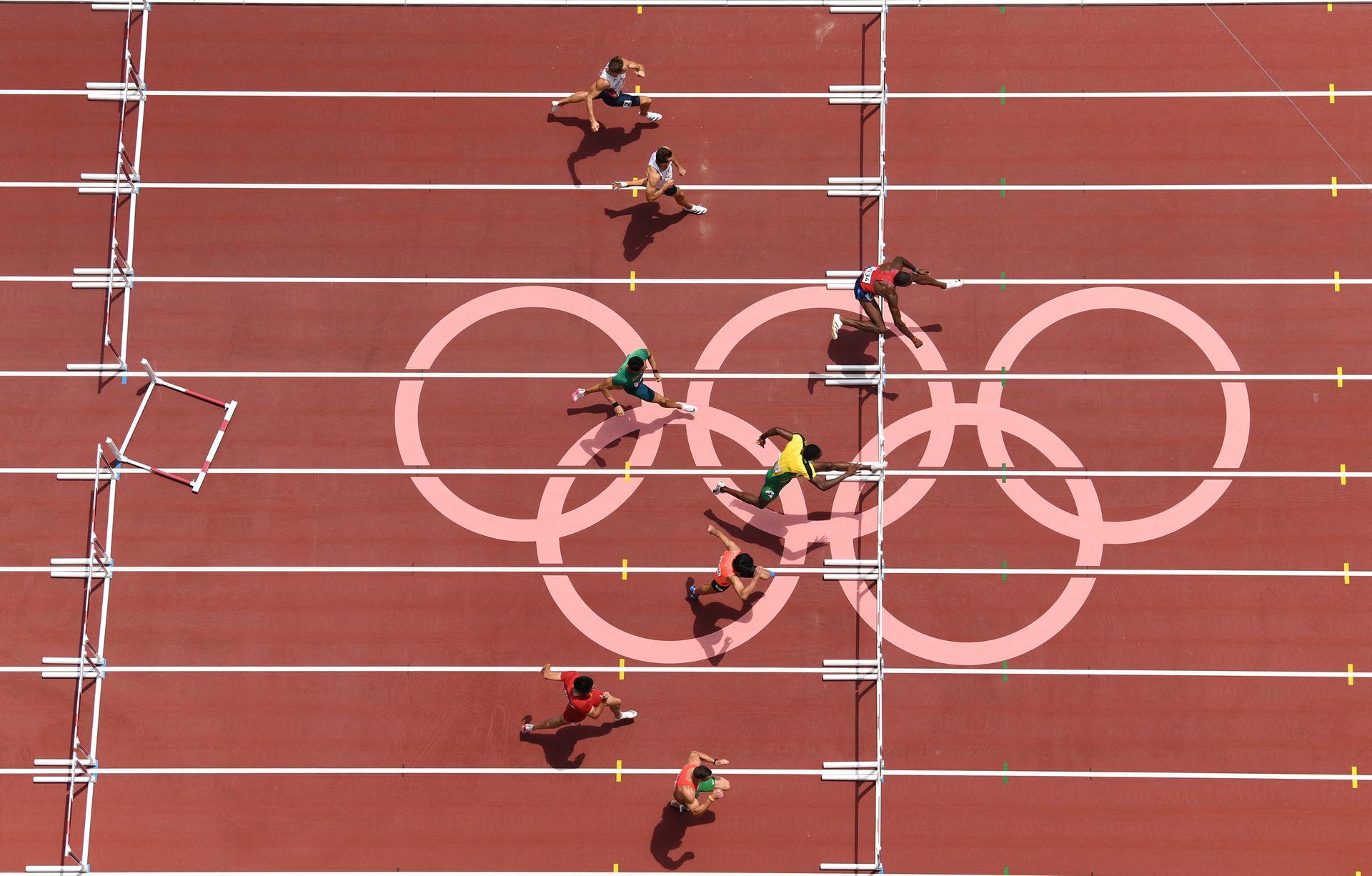 Grant Holloway (R) de EE. UU. Compite para ganar las semifinales masculinas de 110 metros con vallas