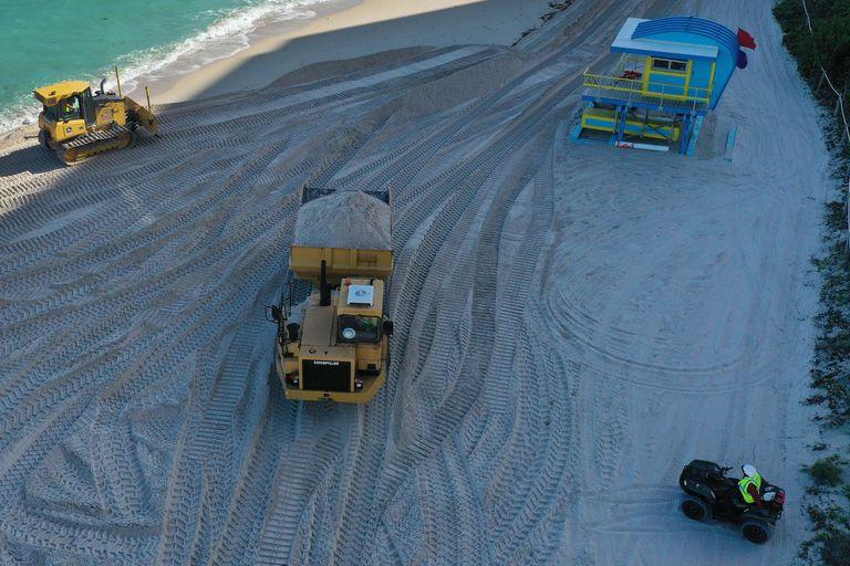 Los camiones mueven toneladas de arena
