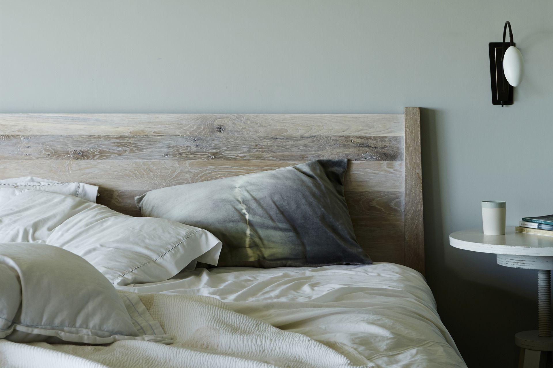 El cuarto principal en el primer piso, con cama de madera y mesita regulable (todo, de Canvas Home). Almohadas batik (Kirsten Hektermann) y lámpara 'Scorpion' (Ochre).