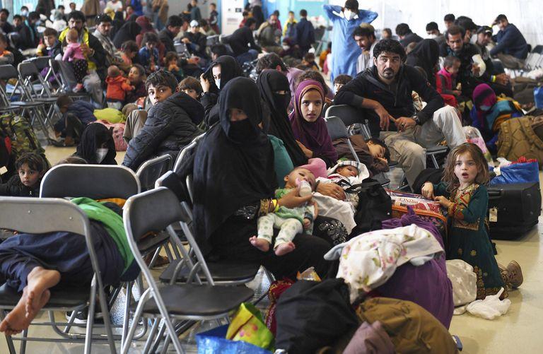 Refugiados afganos esperan a ser procesados dentro del hangar 5 en la base aérea Ramstein, el miércoles 8 de septiembre de 2021, en Alemania. (Olivier Douliery/Pool via AP)