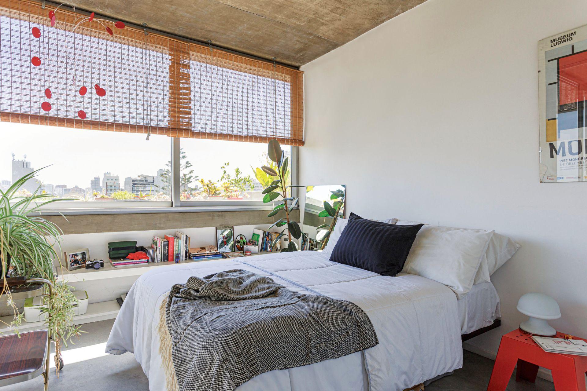 Sobre la cama, manta de algodón con flecos (Elementos Argentinos). Junto a la persiana de mimbre, móvil (Cuerpos móviles).