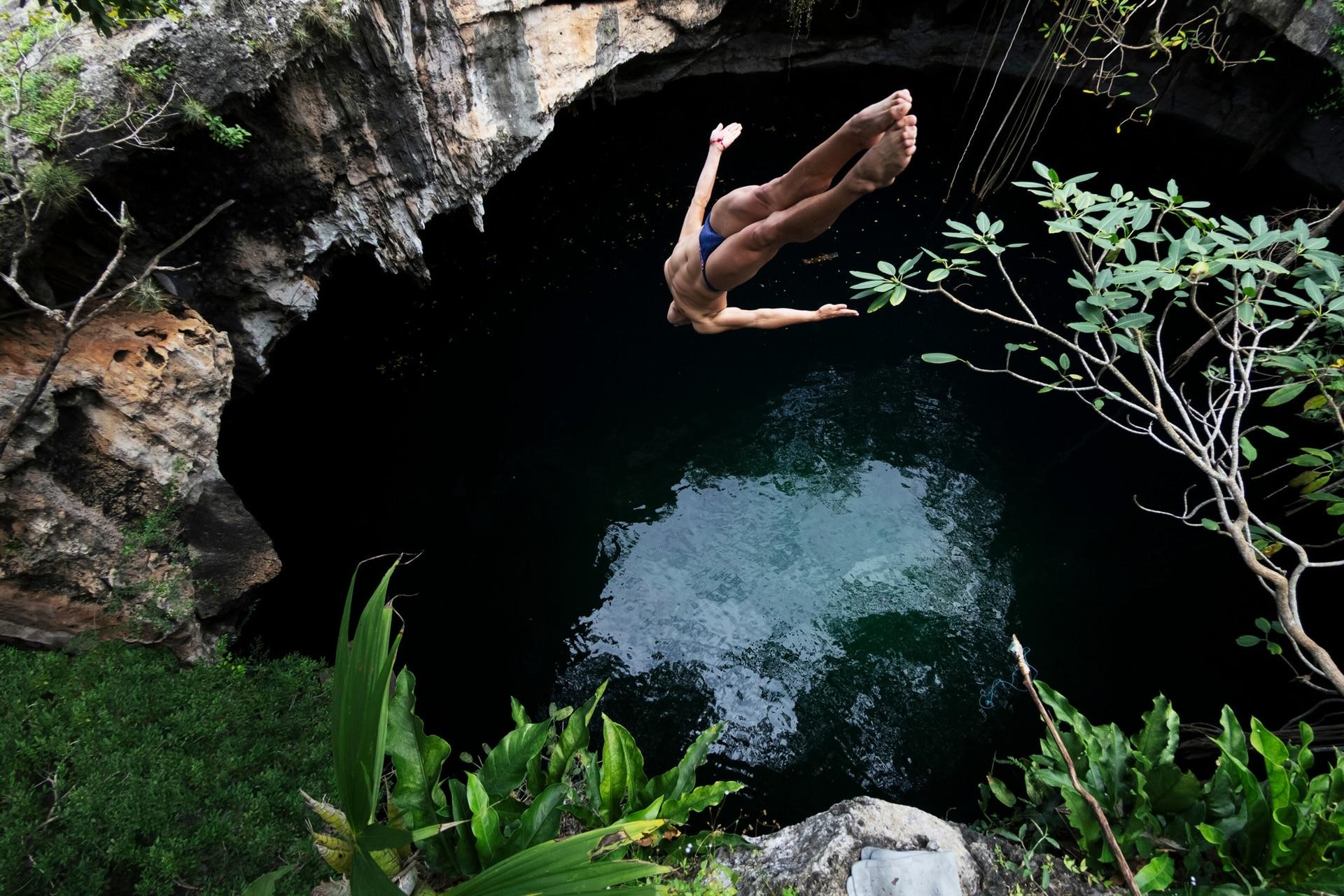 """Jonathan Paredes realiza un clavado estilo """"Barani"""" que consiste en un salto mortal adelante de medio giro en el Cenote Suhen, en Yucatán"""