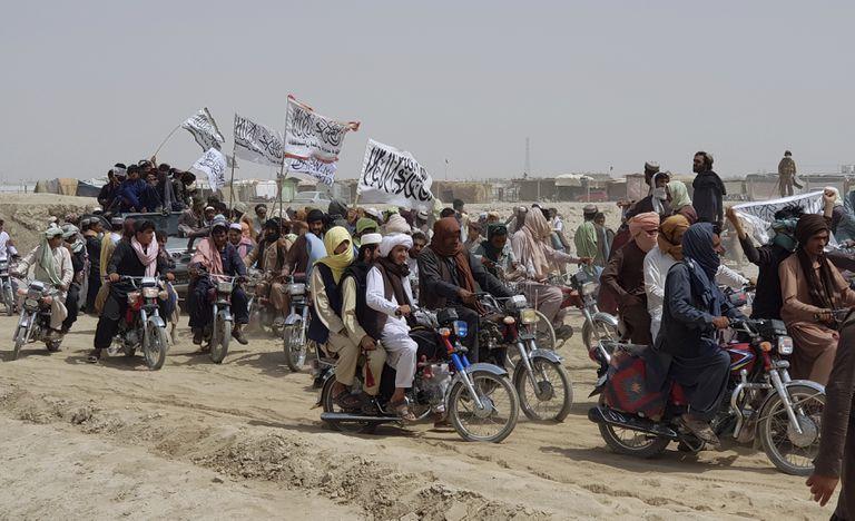 En esta fotografía de archivo del 14 de julio de 2021, los partidarios de los talibanes llevan sus banderas blancas distintivas después de que los talibanes dijeron que tomaron la ciudad fronteriza afgana de Spin Boldaka frente a la ciudad de Chaman, Pakistán.