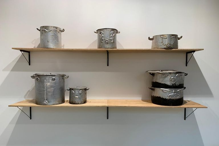 Chaile compró baterías de cocina nuevas y las cambió en comedores populares por las ollas de aluminio abolladas y quemadas por los años de alimentar a quienes no tienen qué comer; a estas piezas les grabó rostros infígenas y escribió una leyenda