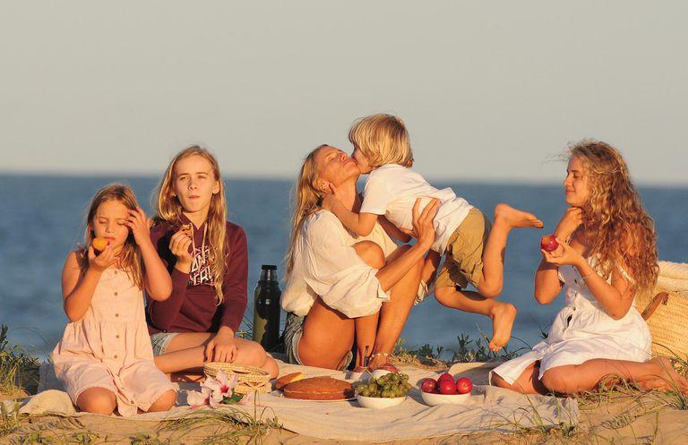 Picnic y amor sobre la arena. Carola posa con sus hijos mientras toman la merienda.