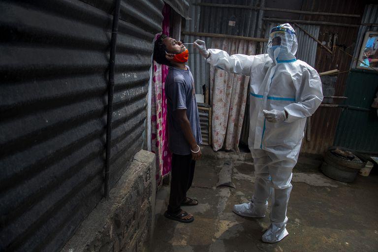 Un trabajador de la salud, con un traje de protección, toma una muestra nasal a un hombre para una prueba de COVID-19 en el estado de Assam, India