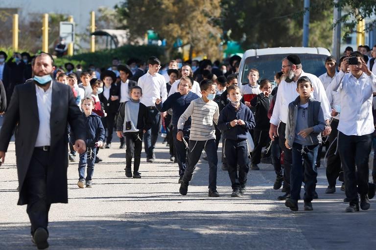 Los niños de la comunidad judía ultraortodoxa israelí caminan frente a una escuela judía talmúdica, que estaba abierta en violación de las reglas de confinamiento, luego de su cierre por las fuerzas de seguridad israelíes, en la ciudad de Ashdod el 22 de enero de 2021