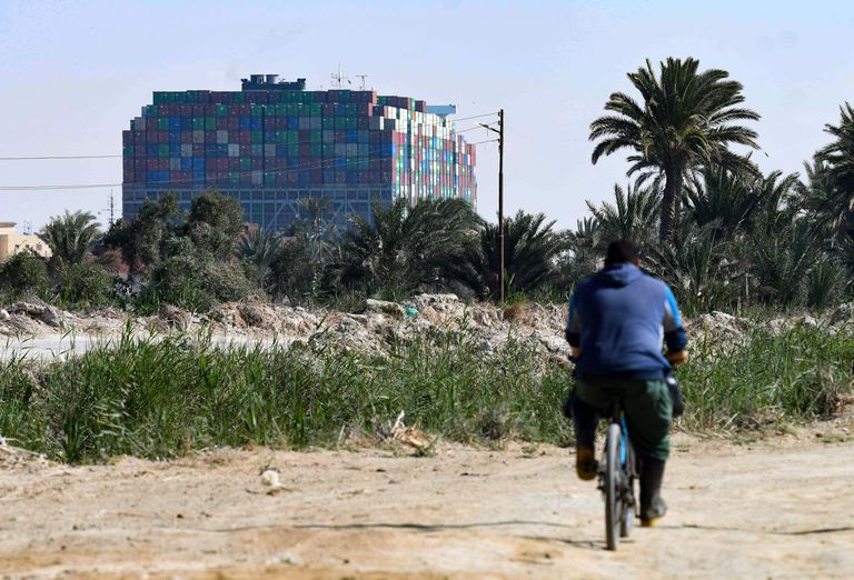 Se muestra un edificio en la ciudad de Ismailiya, en el noreste de Egipto, frente al buque portacontenedores MV 'Ever Given' (Evergreen), propiedad de Taiwán, un buque de 400 metros (1.300 pies) de largo y 59 metros de ancho, alojado de lado e impidiendo todo el tráfico a través de la vía fluvial del Canal de Suez de Egipto, The MV Ever Given, which is longer than four football fields, has been wedged diagonally across the span of the canal since four days, blocking the waterway in both directions. (Photo by Ahmad HASSAN / AFP)