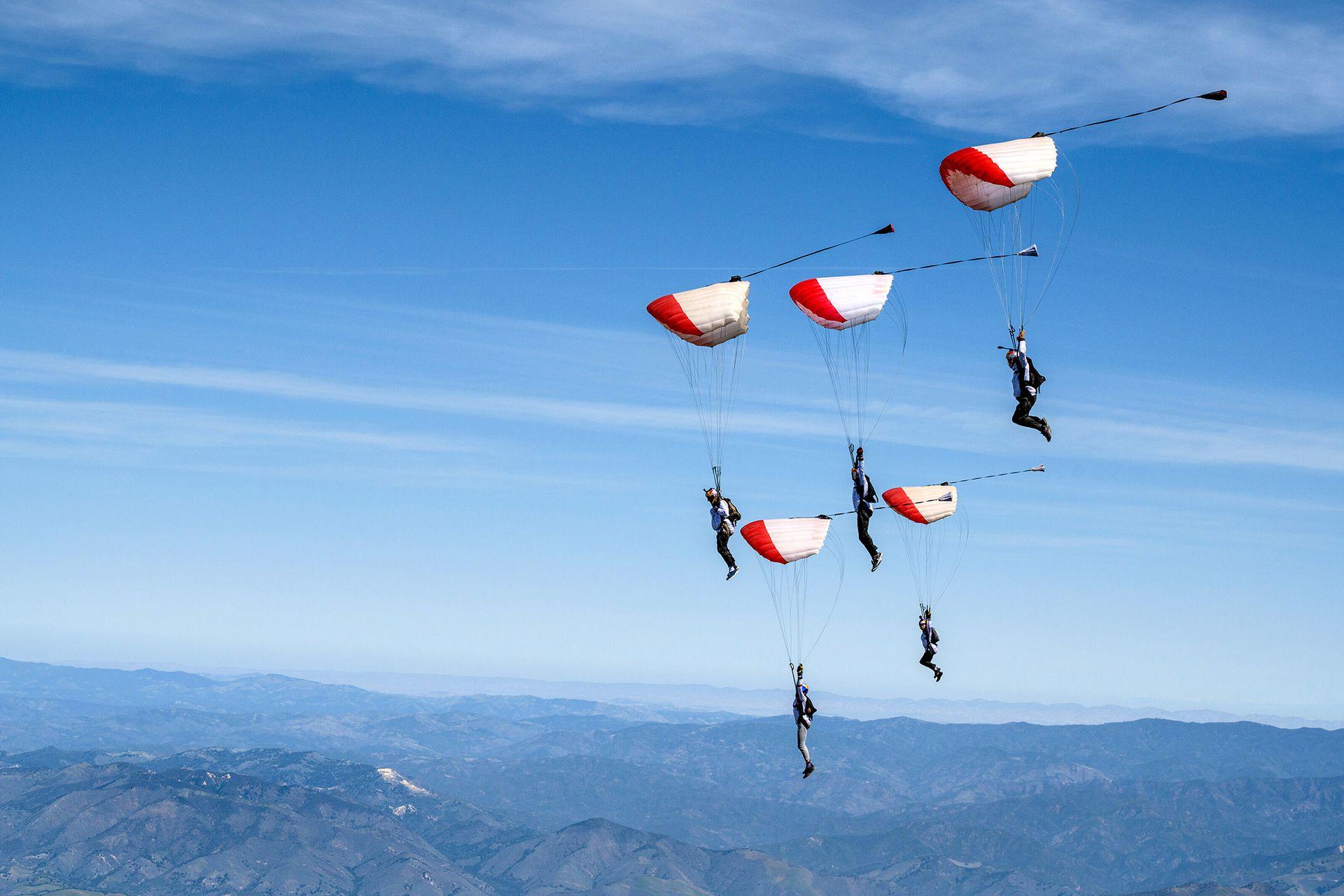 Los paracaidistas experimentados realizan una figura con el paisaje de Los Alamos al fondo