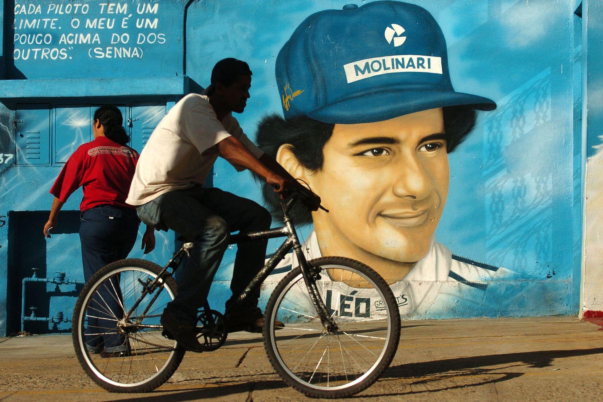 La gente pasa frente a un mural recordatorio del campeón brasileño de F1, Ayrton Senna. En San Pablo, Brasil