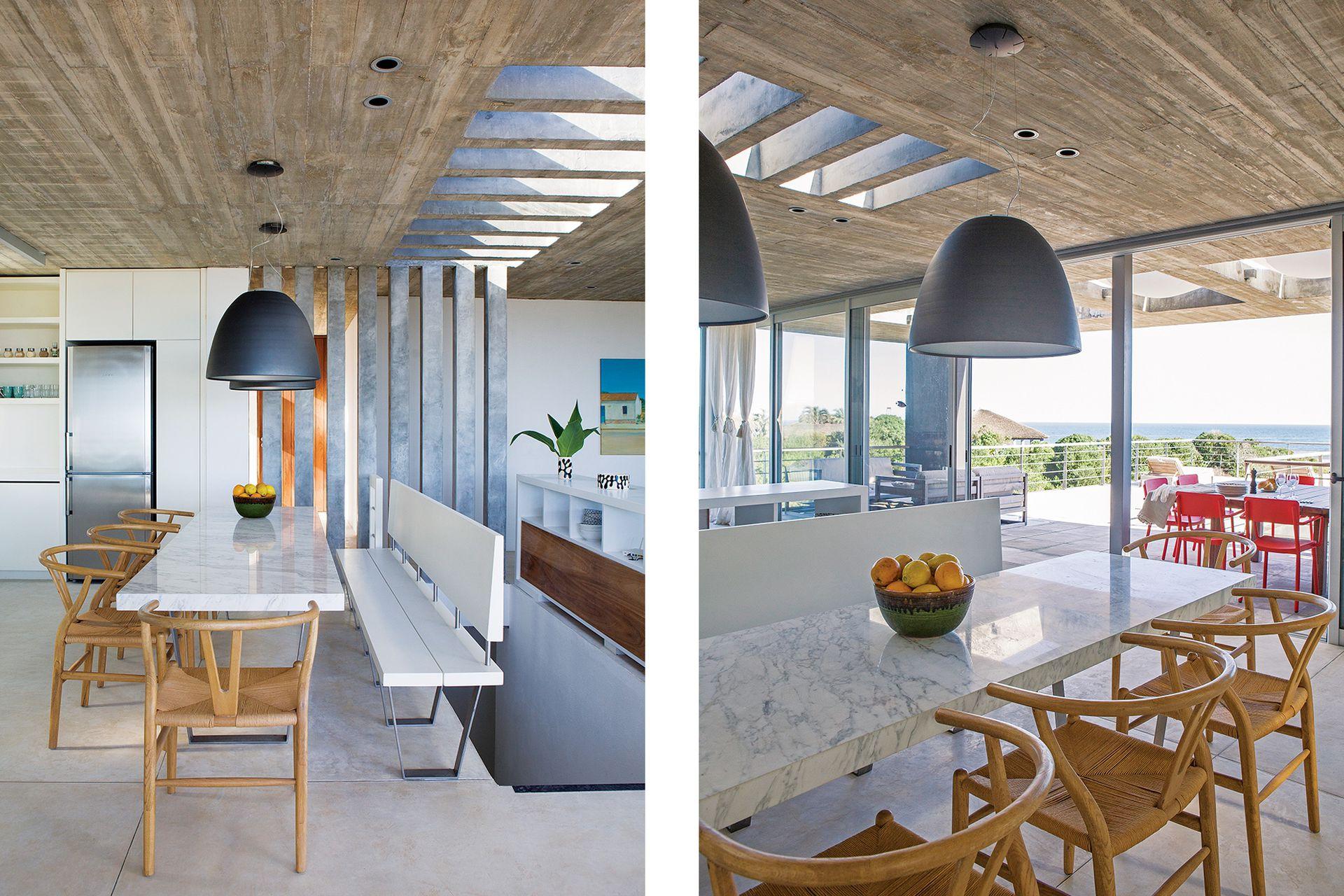 Mesa de mármol de Carrara (Laviere Vitacca) con sillas 'Wishbone' (Mad for Modern) y un banco laqueado que separa del ojo de la escalera. Los spots embutidos en la losa se complementan con lámparas que dan luz puntual y destacan la mesa de comedor.