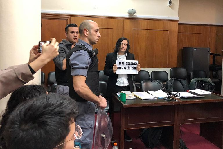 """Cuando ingresó al Tribunal, Aldana volvió a mostrar el cartel que dice """"Sin defensa no hay juicio"""", como hizo en audiencias anteriores"""