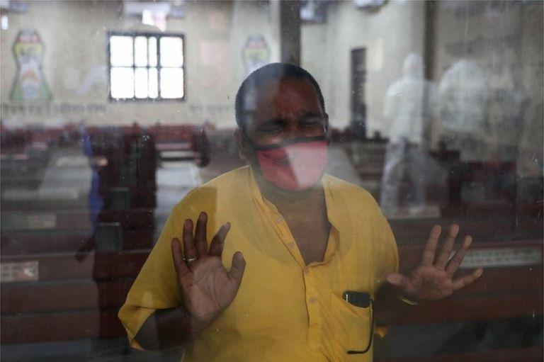 El pariente de un familiar que murió de coronavirus observa a través de una ventana cómo preparan a la víctima para su cremación