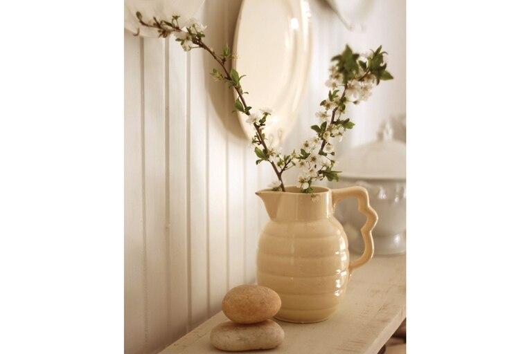 A un par de ramas de cerezos en flor, nada hay para agregarles. Sí, en cambio, elegirles un bello contenedor, como esta pieza de cerámica color marfil, que les ofrece un sutil contraste.