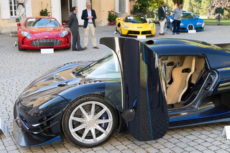 Las personas que miran un Koenigsegg One: 1 modelo 1 delante de un Aston Martin One-77 Coupe (2011), rojo, Ferrari LaFerrari (2015), amarillo, y un Bugatti Veyron EB 16.4 Coupe (2010), azul.