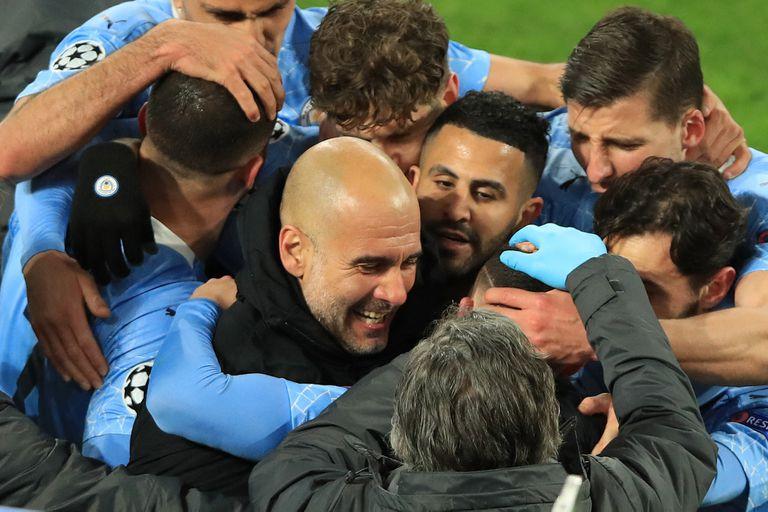 Guardiola, en el medio de los abrazos de los jugadores de Manchester City, que volvió a consagrrse campeón de la Prremier League.