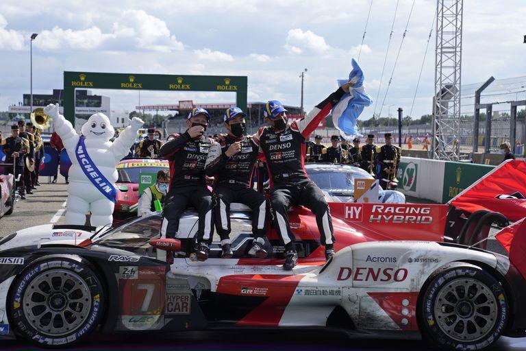 Mike Conway, Kamui Kobayashi y Pechito López, con la bandera argentina en su mano izquierda, celebran la victoria en Le Mans; el trinomio logró reponerse de las frustraciones de los tres años anteriores y se impuso por dos vueltas de diferencia sobre el auto N°8 de Toyota Gazoo Racing