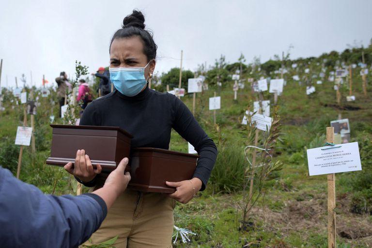 Vista aérea que muestra a familiares de víctimas del Covid-19 esparciendo sus cenizas en huecos donde plantan árboles durante un homenaje a sus seres queridos y como parte del programa Cenizas Fuente de Vida de la ONG ambiental Colombia Life Reserve en la reserva natural de Páramo de Guerrero en el municipio de Cogua, cerca de Bogotá el 21 de junio de 2021; Colombia registró más de 100.000 muertes por Covid-19. (Foto de Raúl ARBOLEDA / AFP)