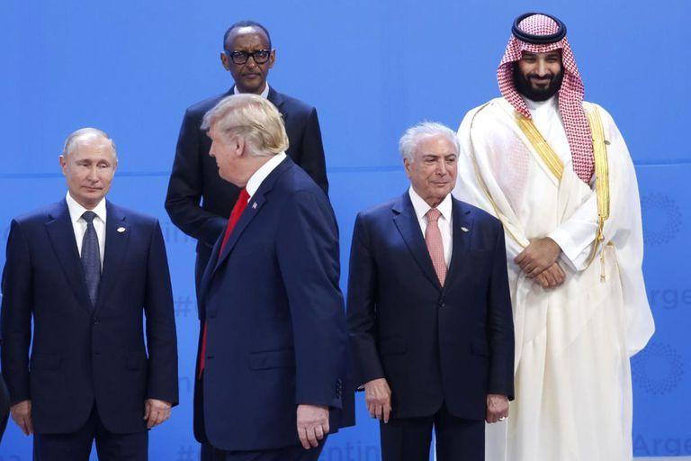 Vladimir Putin y Donald Trump intercambian miradas mientras se acomodan para la foto de familia