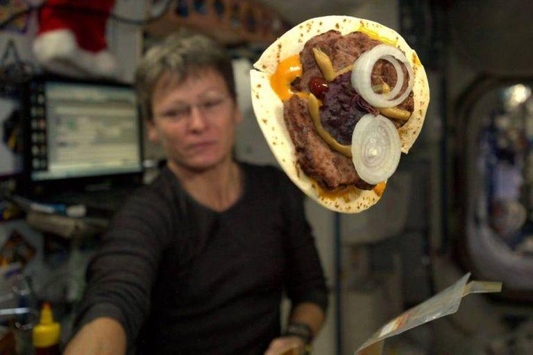 La comandante de la Expedición 51, Peggy Whitson, muestra la hamburguesa que preparó con una tortilla