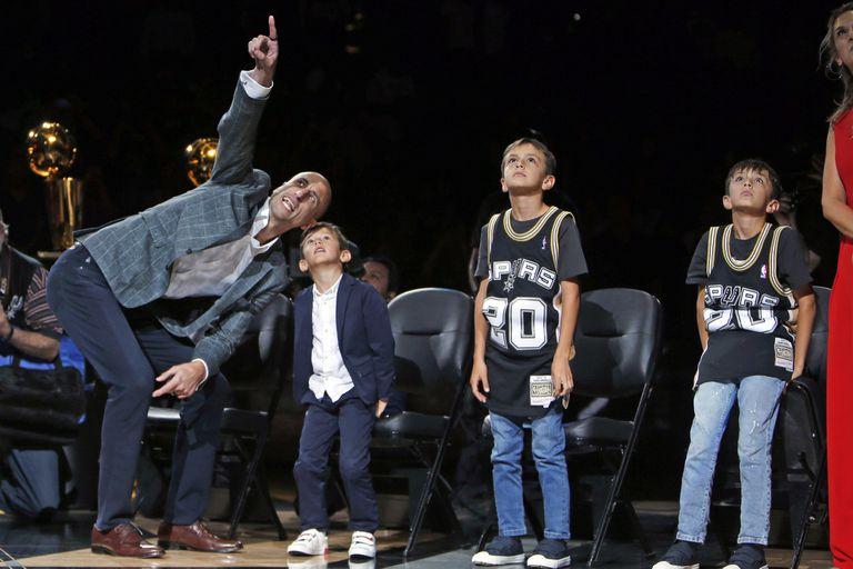 Con sus hijos, viendo la camiseta número 20 en la cima del estadio