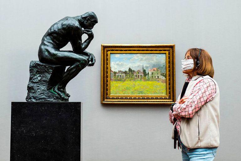 """Una visitante con barbijo mira la escultura icónica de Auguste Rodin """"El pensador"""" en la Old National Gallery en Berlín"""