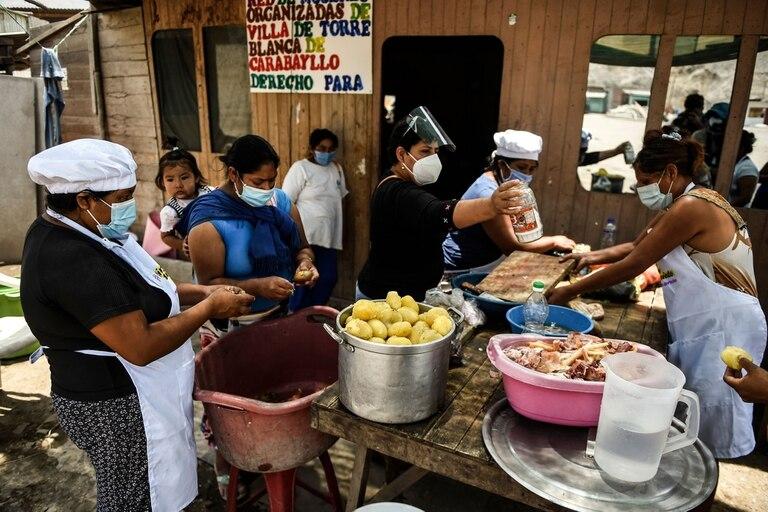Mujeres voluntarias preparan la comida en un comedor en las afueras de Lima. La economía se deterioró fuertemente durante la pandemia, que ahora está en niveles récord