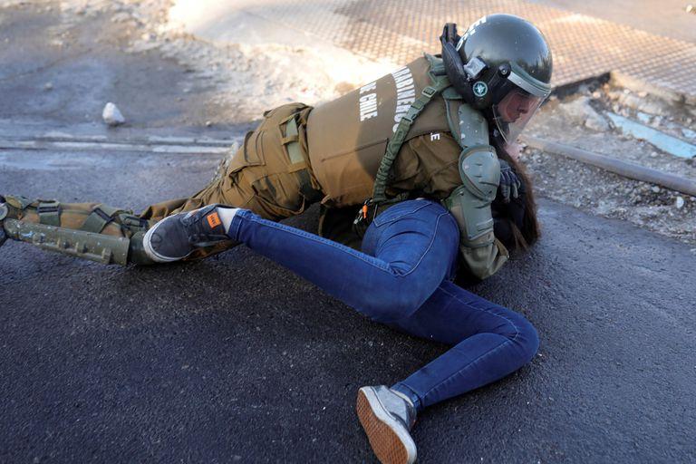 Un carabinero detiene a una manifestante en las calles de Santiago