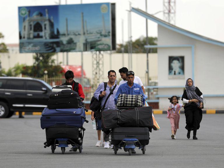 Pasajeros se dirigen a la terminal de salidas del aeropuerto internacional Hamid Karzai en Kabul, Afganistán, para abandonar el país