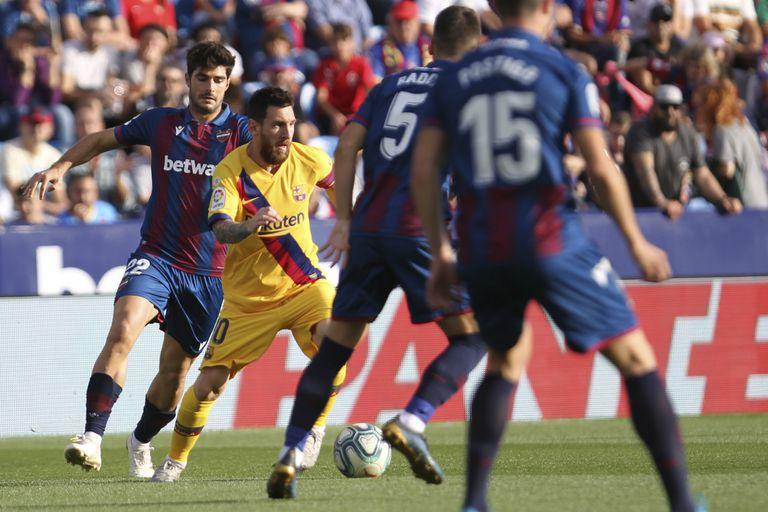 Messi maniobra entre varios jugadores de Levante